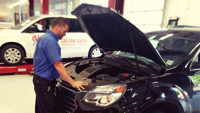 Rich Young, car care manager at the new AAA Car Care, Insurance and Travel Center in North Plainfield, takes a look under the hood of a car brought in for service.