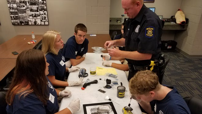 Participants in last year's Westland Police Department Youth Academy practice fingerprinting techniques. The department is now accepting applications for this year's academy.