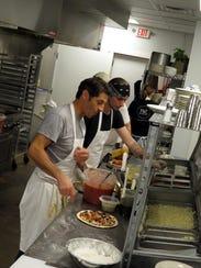 Hubert Mussat, left, works with his crew in the kitchen