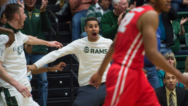 Injured CSU basketball player Gian Clavell cheers from the bench after teammate John Gillon scores on a breakaway dunk near the end of the Rams' 86-69 win Tuesday night over New Mexico. Clavell was the Rams' leading scorer before suffering season-ending injuries in mid-December.