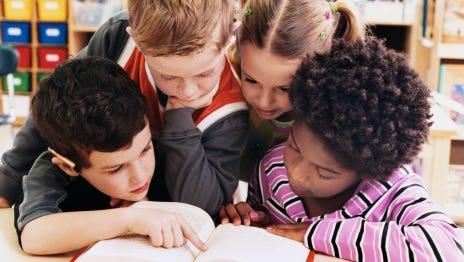 Stock image showing students reading together.