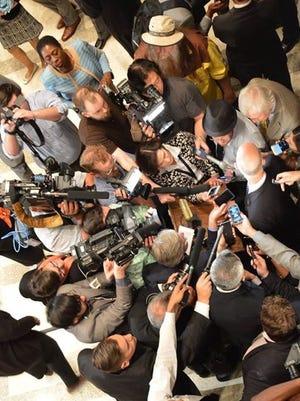 Reporters swarm Gov. Rick Scott.