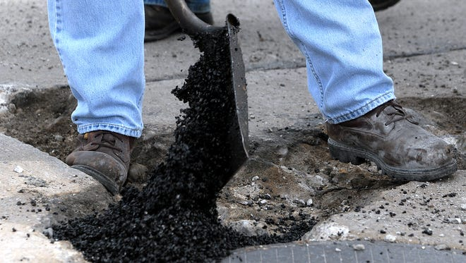 Highway worker drops a shovelful of patching material into a pothole.