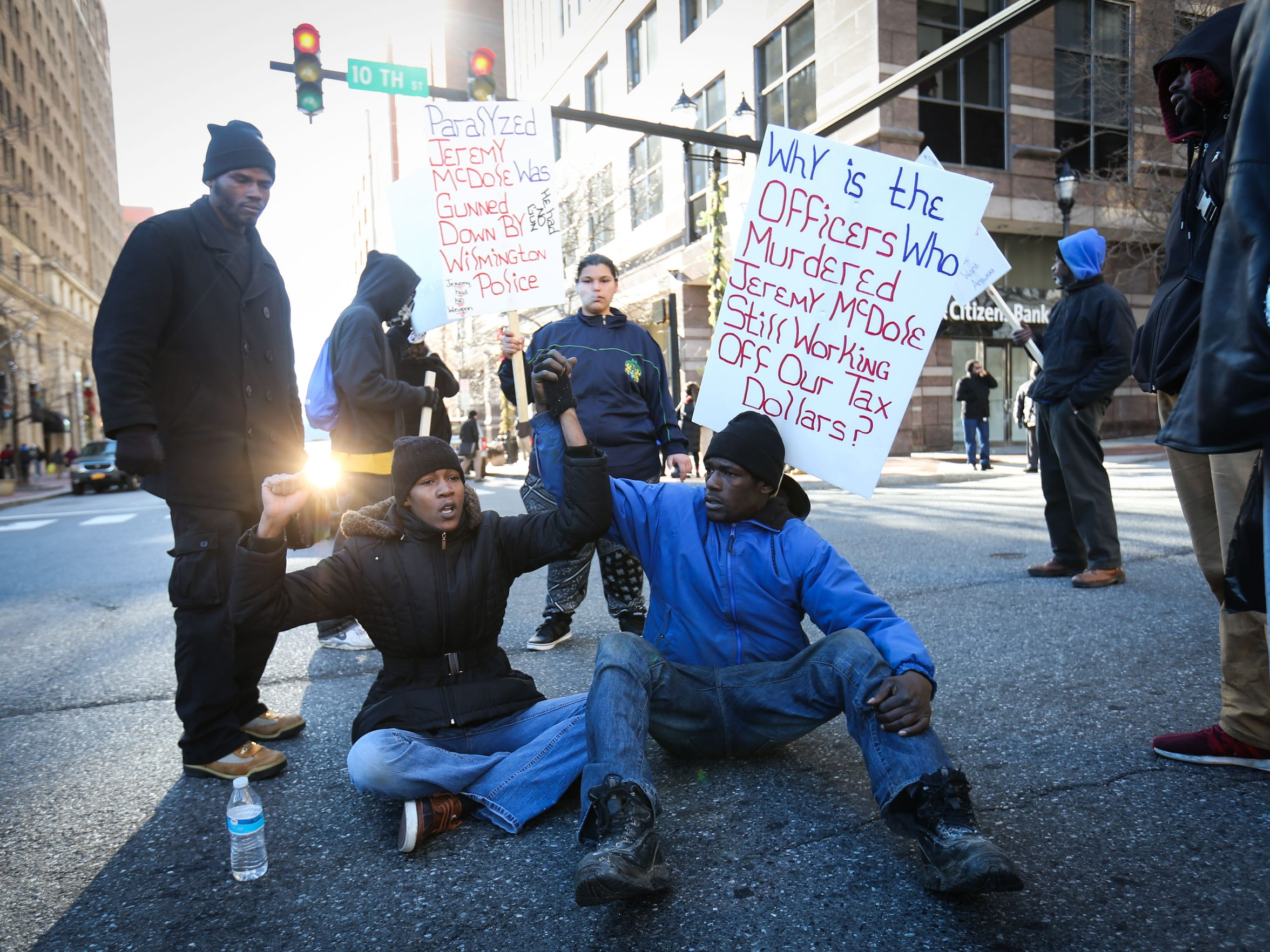 Keandra McDole and Robert Berry sit down at the intersection of Market and 10th streets in Wilmington during a protest in January.