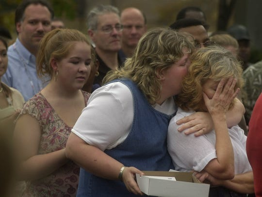 Diana Powers, right, is comforted by her daughter Amy during the dedication ceremony for her brother, Ray Batzel,   in Webster on Friday, Oct. 31, 2003. The Ray Batzel Memorial Garden is located at Building 224.