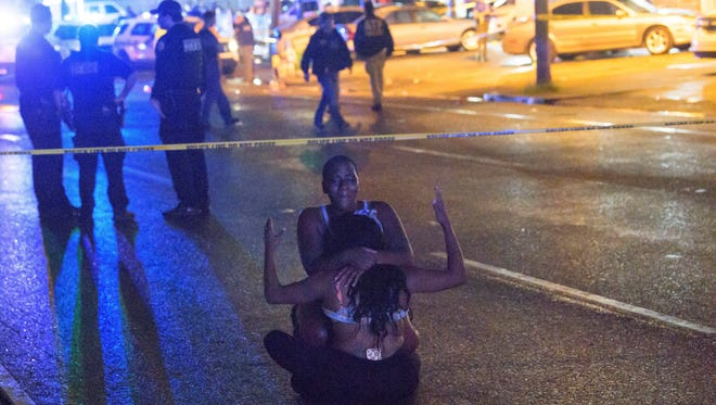 People react at the scene of a shooting in New Orleans on Saturday.