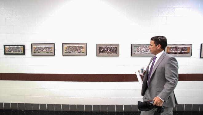 Marty Pollio walks past a row of senior class photos at Jeffersontown High School, a school where he was principal for eight years. Pollio is the acting Superintendent of Jefferson County Public Schools. July 25, 2017