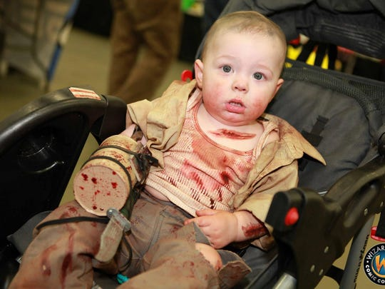 "A baby dressed up as Merle Dixon from ""The Walking Dead"" at a Wizard World Comic Con."
