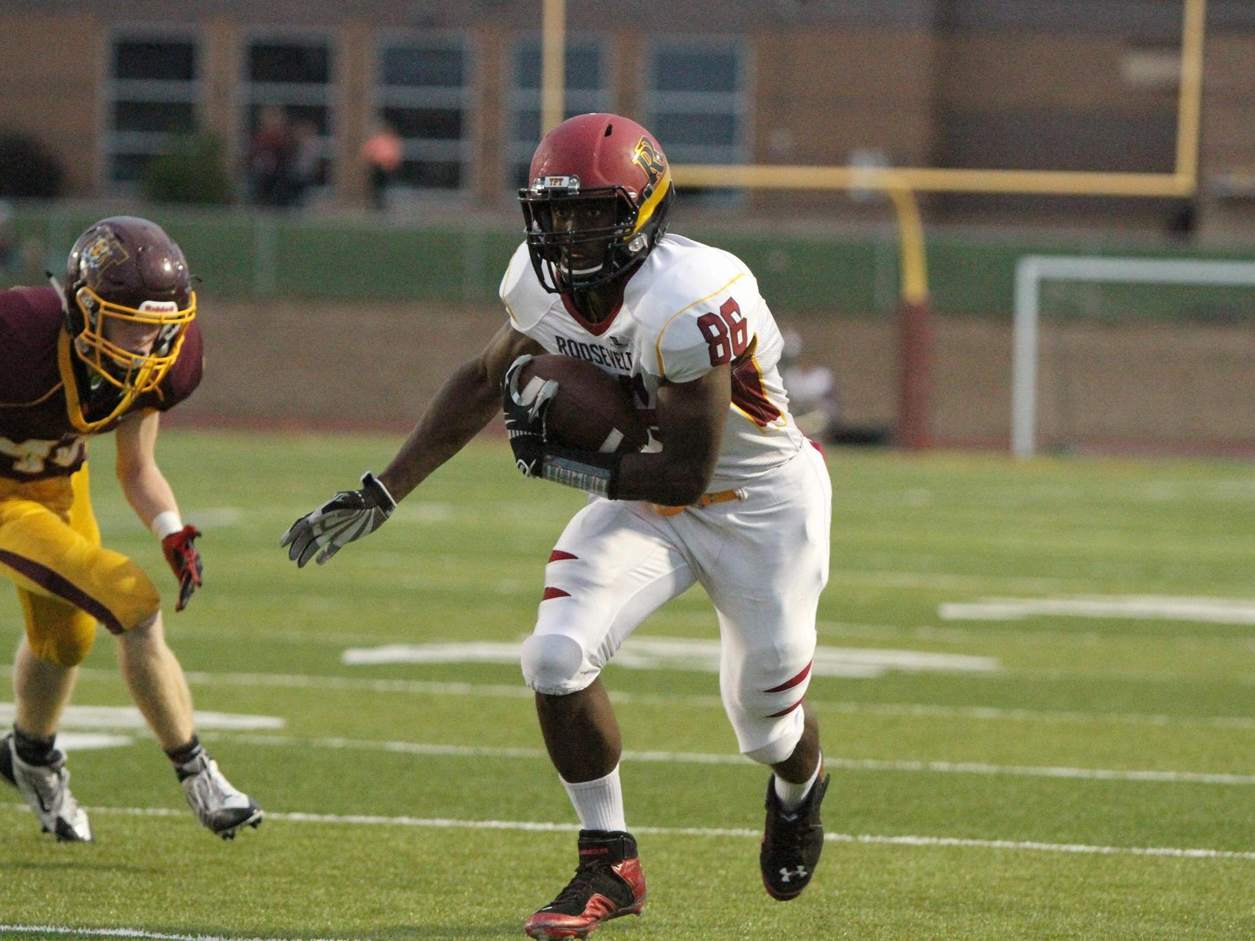 Roosevelt's DeMareio Hester moves up field after catching a pass as Harrisburg's Michael Curry pursues.
