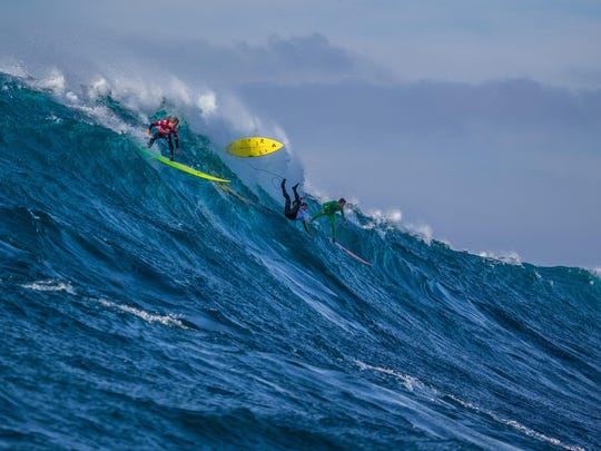 Josh Kerr of Australia, now residing in California (red), Carlos Burle of Brasil (white) and Nic Lamb of the USA (green) ride a wave together during the Final of the Todos Santos Challenge in monstorous 30-40 foot surf on Sunday, January 17, 2015.