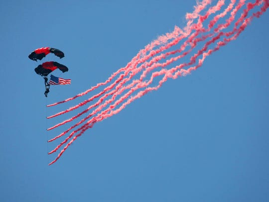 Members of the U.S. Army Black Daggers parachute team open the show in 2011 with a jump that included the American Flag and red smoke.