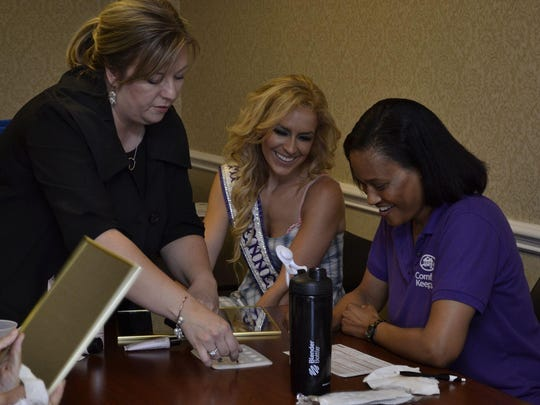 Mary Kay Sales Director Jennifer Hooper, left, gives makeup advice to domestic abuse survivor Daphnne Lelcesona, with help from Mrs. Tennessee International Deanna Loveland.