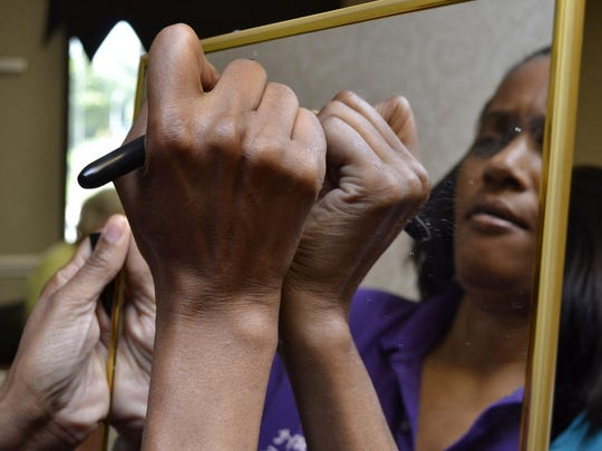 "Domestic abuse survivor Daphnne Lelcesona writes ""I am beautiful"" on her mirror at the self-esteem workshop."