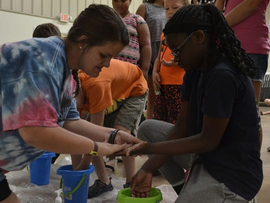 Dayshore Assistant Director Eva Pray helps camper Jekylin Akins, 11, wash her hands during the morning Bible session Tuesday at First United Methodist Church in Alamo.