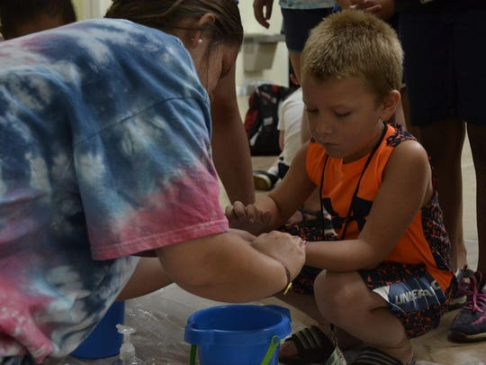 Dayshore Assistant Director Eva Pray helps a camper wash his hands during the morning Bible session Tuesday at First United Methodist Church in Alamo.