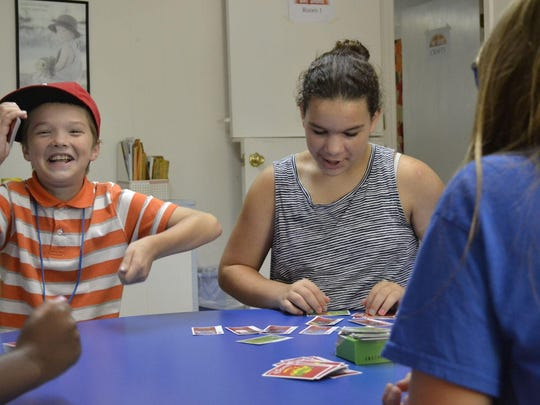 From left to right, Nathan Poe, 10, Morgan Mosier, 10, and Natalie Moncier, 10, play Apples to Apples during a morning activity period at First United Methodist Church in Alamo.