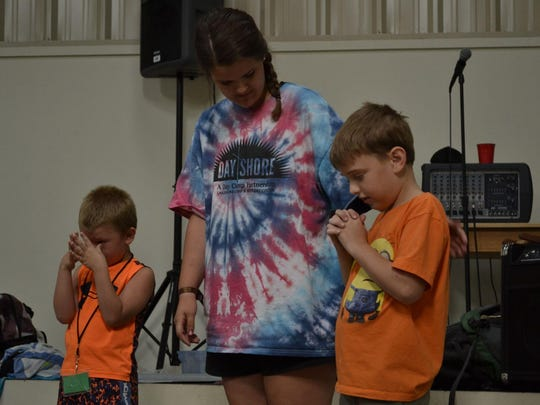 Dayshore Assistant Director Eva Pray prays with campers before the morning Bible session Tuesday at First United Methodist Church in Alamo.