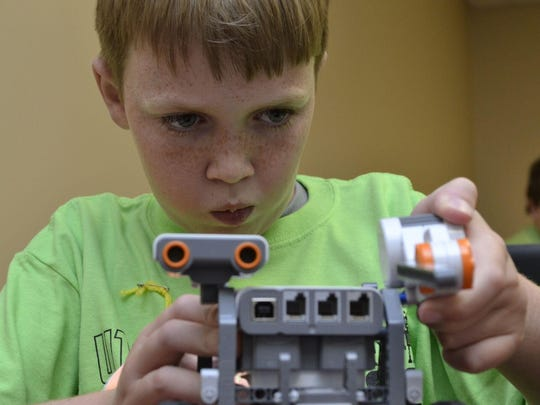 Drake Wallace, 10, puts an arm on his robot at the robotics camp Monday afternoon at the University of Tennessee at Martin Extension Center.