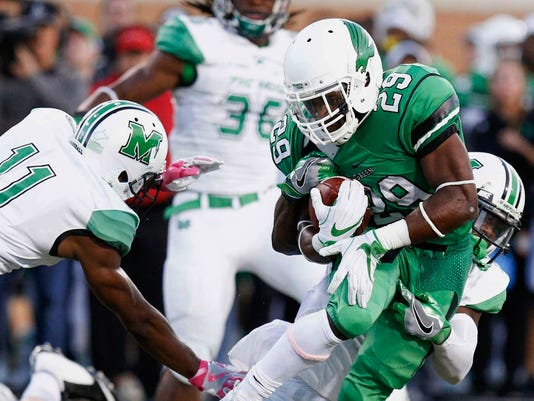 FILE- In this Oct. 8, 2016, file photo, North Texas running back Willy Ivery (29) rushes the ball, while Marshall safety C.J. Reavis (1) wraps him from behind in an NCAA college football game in Denton, Texas. North Texas will play in the Heart of Dallas Bowl after going 5-7, and the game will be a rematch against an Army teams it met six weeks ago. (Jeff Woo/The Denton Record-Chronicle via AP, File)