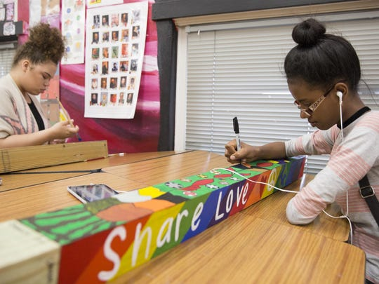 """Jaidah Robinson and Danait Haile, student in Joleen Weller's art class at East High School, create """"peace poles"""" to be displayed in the community."""