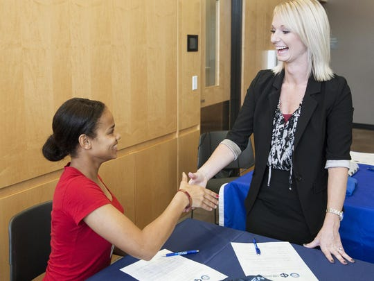 Central Campus Urban Teacher Academy senior Mariah Ster is congratulated by  Nikole Cummins, an admissions representative from Iowa Central Community College in Fort Dodge, during a ceremony Wednesday at Central Campus.
