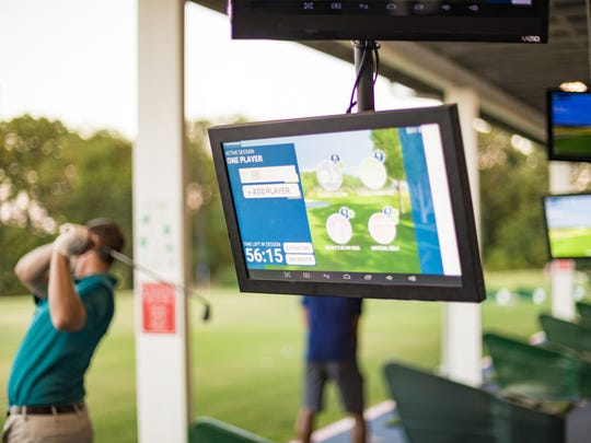 A Toptracer monitor hangs in a hitting bay.