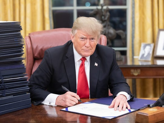 President Trump signing paperwork in the Oval Office. Official White House Photo by Shealah Craighead.