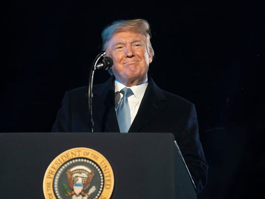 A smiling President Trump standing behind the presidential podium.