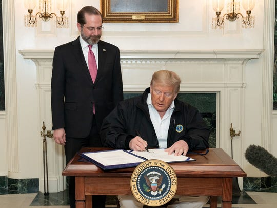 President Trump, flanked by Secretary of Health and Human Services Alex Azar, signs the coronavirus bill into law.