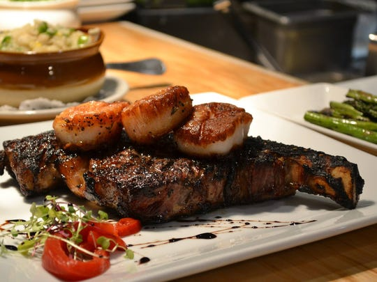 An all-natural cowboy steak, which is a bone-in rib-eye, topped with seared scallops at Prime 13 in Point Pleasant Beach.