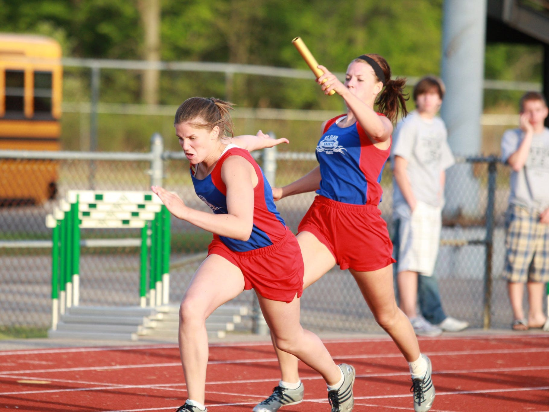 Addie Ingles passes to Courtney Ingles during a track and field event.