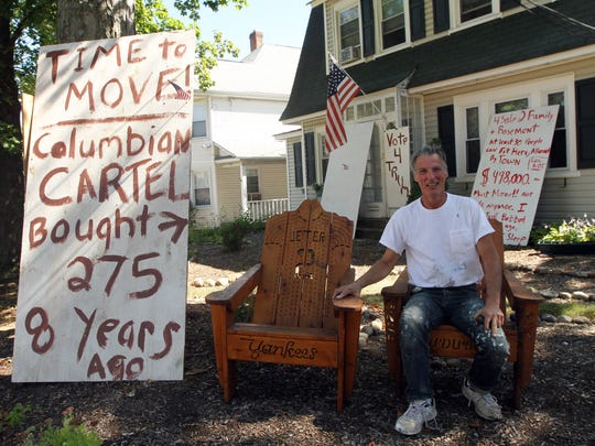 Morristown resident and Speedwell Avenue homeowner Gregg Bruen puts up signs in front of his home and next door vacant property, blaming rent stacking for lower property values. September 15, 2015, Morristown, NJ.