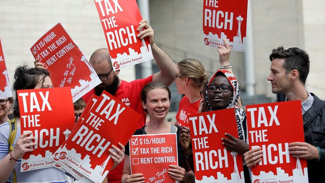 Demonstrators wave signs outside a meeting at which the Seattle City Council unanimously approved a new city income tax on the wealthy.
