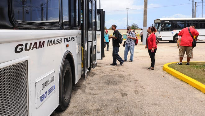 Passengers board and transfer between Guam Mass Transit Authority buses at the stop at the Paseo parking lot on May 13.