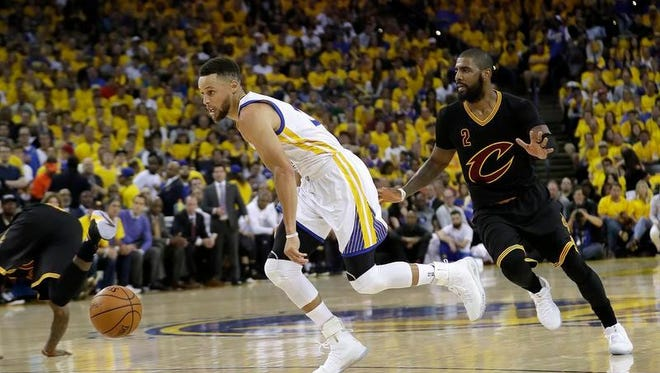Golden State Warriors guard Stephen Curry, left, dribbles past Cleveland Cavaliers guard Kyrie Irving (2) during the first half of Game 2 of basketball's NBA Finals in Oakland, Calif., Sunday, June 4, 2017.