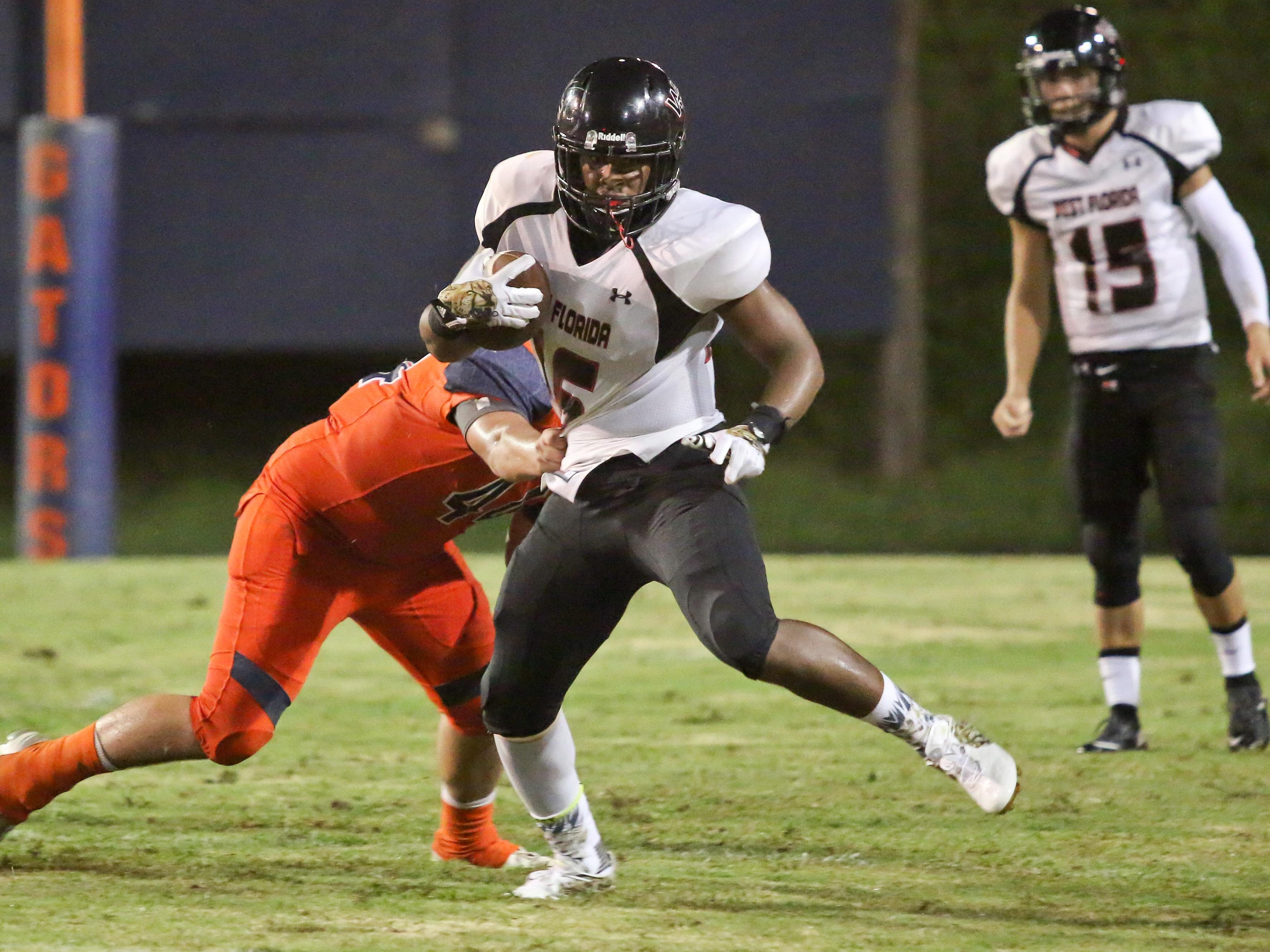 West Florida's Devin Abrams (16) works to get out of the grip of Escambia's Noah Lord (44) Thursday night at Escambia High School's Emmitt Smith Field.