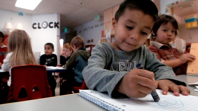 A preschooler at the Teaching Tree day care center draws in his journal in this file photo.