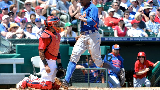 Mets right fielder Curtis Granderson scores in front of Cardinals catcher Yadier Molina.