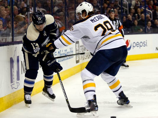 Columbus Blue Jackets forward Cam Atkinson, left, passes the puck past Buffalo Sabres defenseman Jake McCabe during the second period of an NHL hockey game in Columbus, Ohio, Tuesday, March 28, 2017. (AP Photo/Paul Vernon)