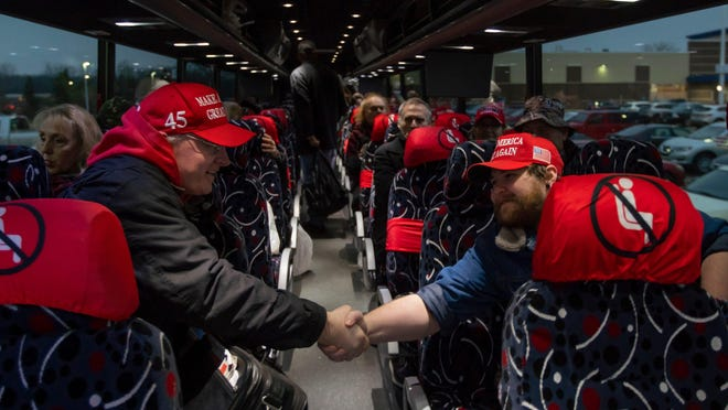 James Madison (right) of Ypsilanti shakes the hand of another trump supporter while wait on board a bus heading to Washington, DC for a March for Trump rally on Monday, January 4, 2021 at the parking lot of Meijer in Shelby Township.