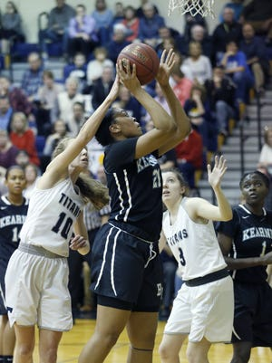 Webster Thomas' Abby Roetker reaches for the ball as Bishop Kearney's Saniaa Wilson aims for the basket in the second quarter at Pittsford Sutherland High School.