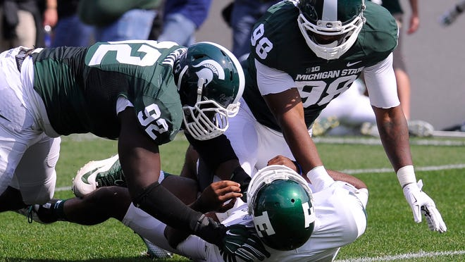 MSU defenders Joel Heath, left, and Demetrius Cooper, right, hit Eastern Michigan quarterback Rob Bolden  at Spartan Stadium Saturday  September 20, 2014 .