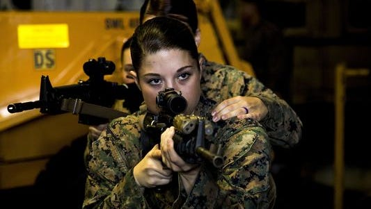 U.S. Marine Cpl. Megan Hirzel, with the 22nd Marine Expeditionary Unit Female Engagement Team, practices room-clearing procedures during a training exercise on May 16, 2016. Congress is considering whether to require all women to register for the possibility of a future military draft.
