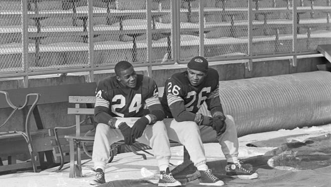Green Bay Packers safety Willie Wood (24) and cornerback Herb Adderley (26) sit on a bench as the team practices at new City Stadium in late December 1962 in preparation for the NFL championship game against the New York Giants in New York.