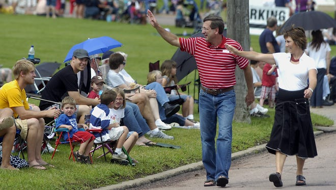 Mayor Mike Huether and his wife, Cindy wave to the crowd at Falls Park during the annual Mayor's 4th of July Parade and Picnic.