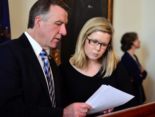 Gov. Phil Scott consults with Brittney Wilson, secretary