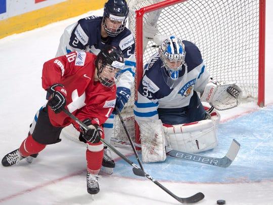 Switzerland's Nico Hischier  tries a wraparound on Finland goaltender Veini Vehvilainen (31) as Finland's Miro Heiskanen (2) defends during the second period of a IIHF World Junior Championships hockey game Saturday, Dec. 31, 2016 in Montreal.