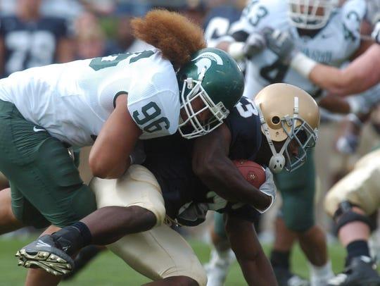 -  -MSU's Domata Peko hits Notre Dame running back