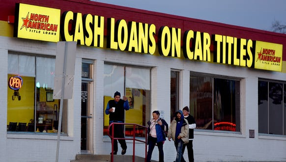 Passersby walk by the North American Title Loans payday