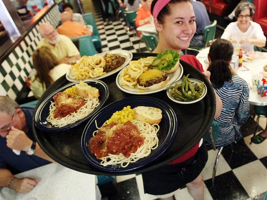 Server Marlene Castille holds a tray of lunch plates at Hub City Diner Wednesday, May 13, 2015, in Lafayette, La.